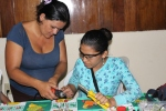 Gregoria, getting some help from a member of the women's group to cut holes in the seeds for her bracelet.